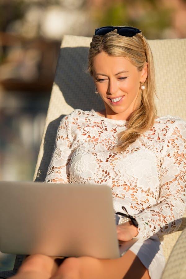 使用便携式计算机的妇女垂直的照片,当坐在轻便折叠躺椅时 图库摄影