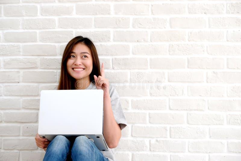 使用便携式计算机的年轻亚裔妇女坐在丝毫前面 免版税库存照片