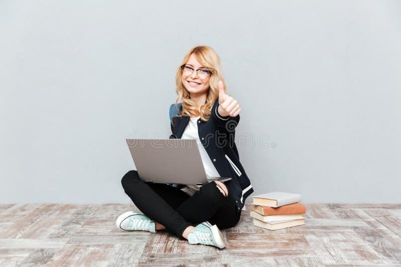 使用便携式计算机的愉快的少妇学生 免版税库存图片