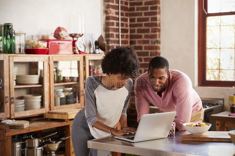 使用便携式计算机的混合的族种夫妇在他们的厨房里 免版税库存图片