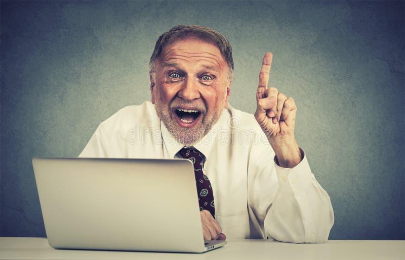 使用便携式计算机的激动的老人有一个想法 库存图片
