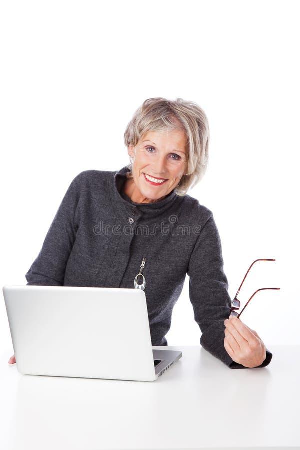 使用便携式计算机的现代资深妇女 库存照片