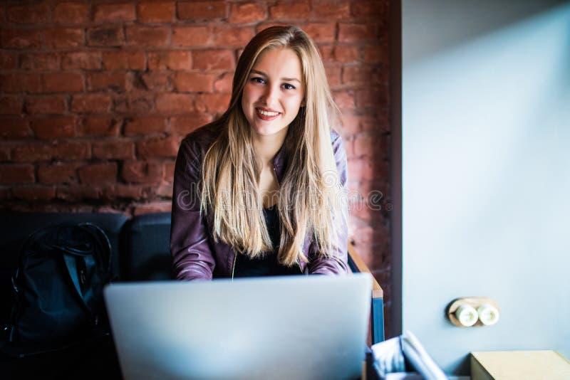 使用便携式计算机的美丽的年轻自由职业者妇女坐在咖啡馆桌 Le愉快的微笑的女孩在网上工作或学习和 免版税图库摄影