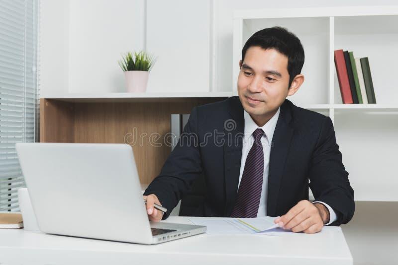 使用便携式计算机的英俊的亚洲商人 免版税库存图片