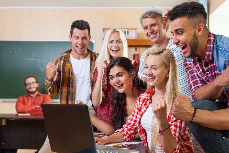 使用便携式计算机的年轻激动的学生团体,混合的族种人愉快的微笑的笑 免版税库存图片