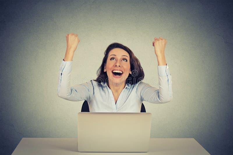 使用便携式计算机,有胳膊的成功的女孩上升了  免版税库存图片