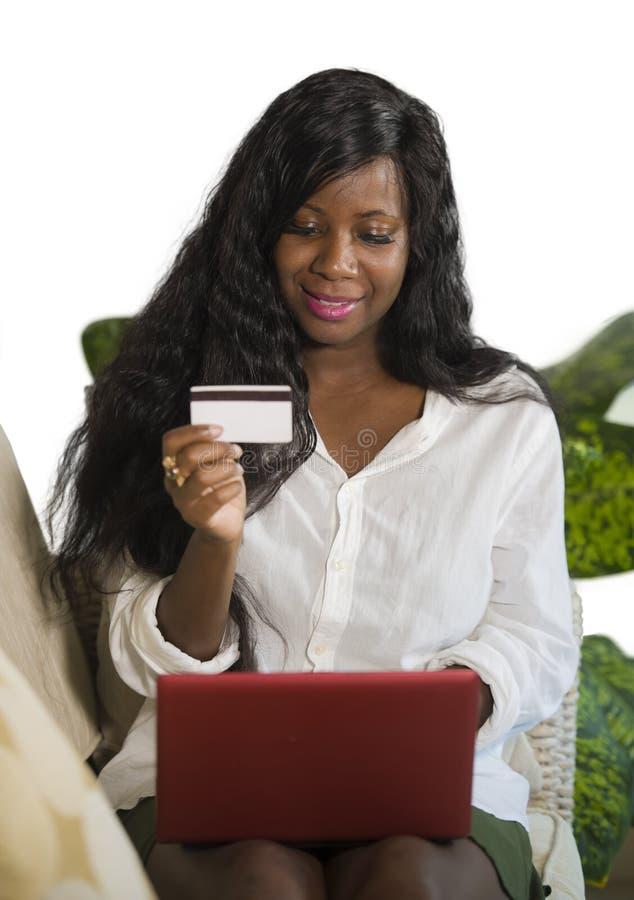 使用信用卡和手提电脑银行业务的年轻愉快和可爱的黑人非裔美国人的妇女在网上和购物在相互 免版税图库摄影