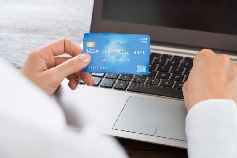 使用信用卡和膝上型计算机的女实业家手 免版税库存照片