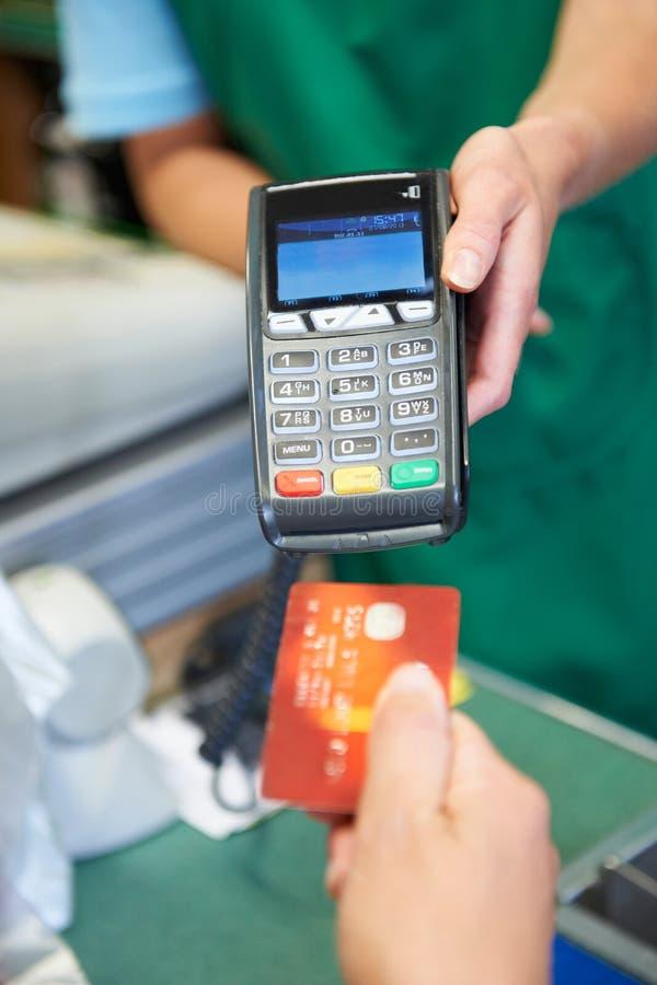 使用信用卡机器的顾客在超级市场支付 免版税库存图片