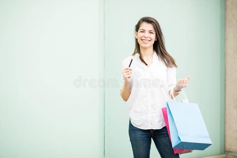使用信用卡的可爱的拉丁妇女为购物 免版税库存照片