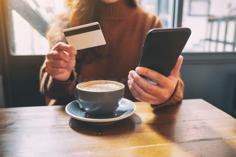 使用信用卡的妇女为购物在网上在手机 免版税图库摄影