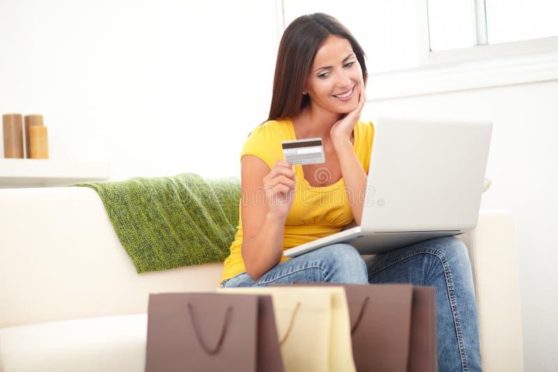 使用信用卡的确信的妇女为购物 免版税库存图片