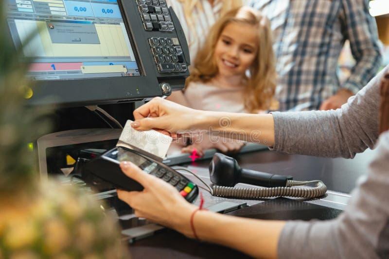 使用信用卡终端的女职工在现金柜台 免版税库存照片