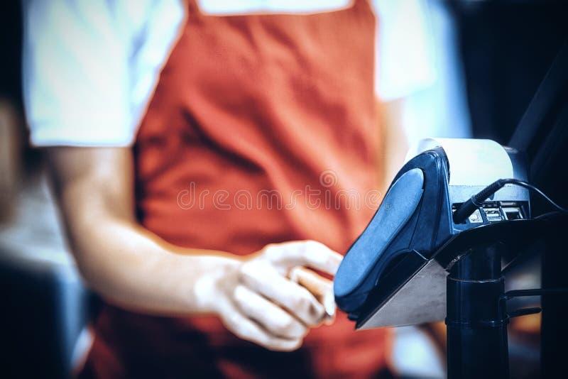 使用信用卡终端的女职工在现金柜台 库存照片