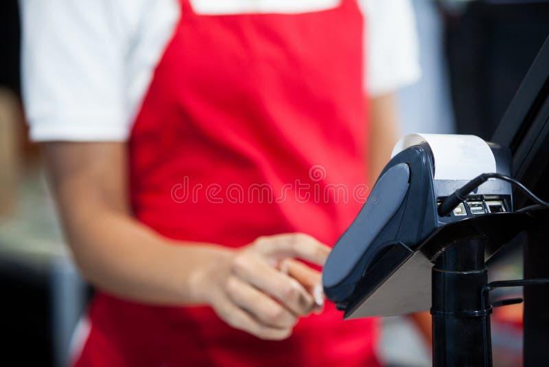 使用信用卡终端的女职工在现金柜台 免版税库存图片