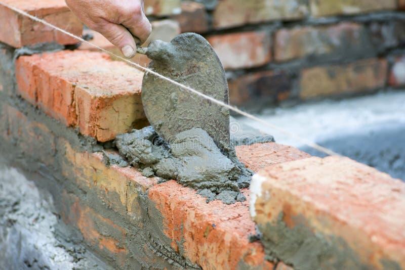 使用修平刀的瓦工轻拍砖水平 递白涂料水泥被修造的墙壁砖新房,瓦工工作者安装bric 免版税图库摄影