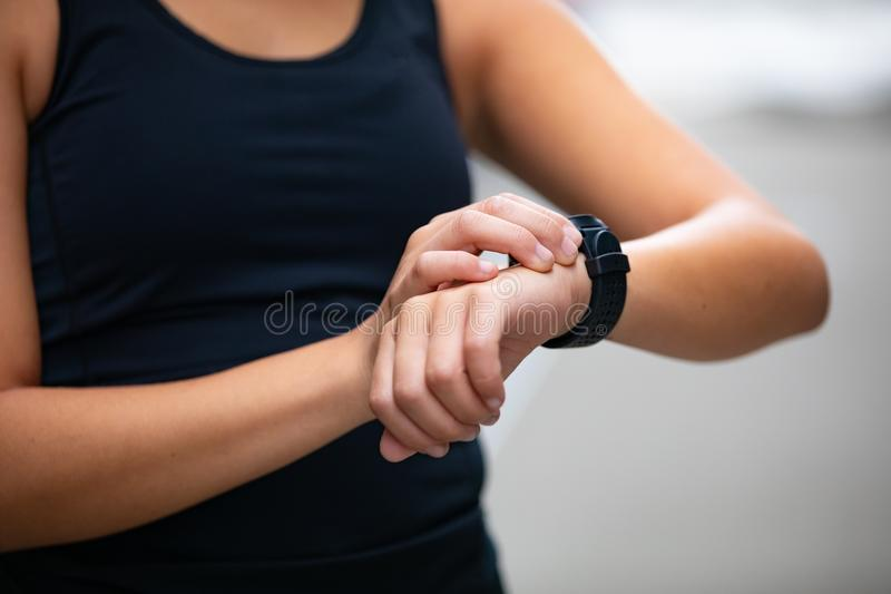 使用健身巧妙的手表设备的妇女特写镜头在跑前 库存照片
