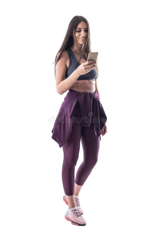 使用健身房或健身应用程序在智能手机的愉快的微笑的适合年轻运动的妇女 免版税库存图片
