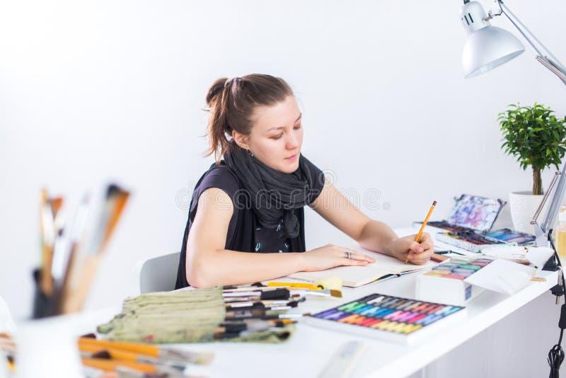 使用写生簿的年轻女性艺术家图画剪影与在她的工作场所的铅笔在演播室 侧视图画象  免版税库存图片