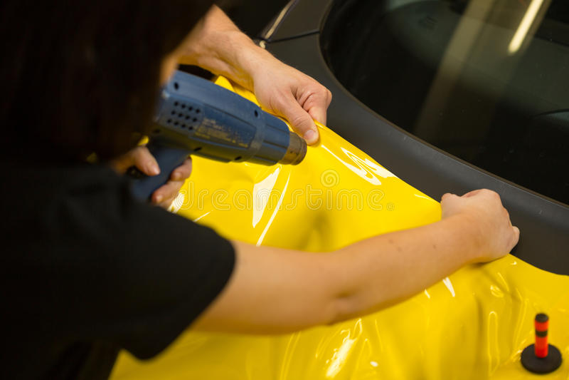 使用准备的热气枪的汽车封皮乙烯基箔 免版税库存照片