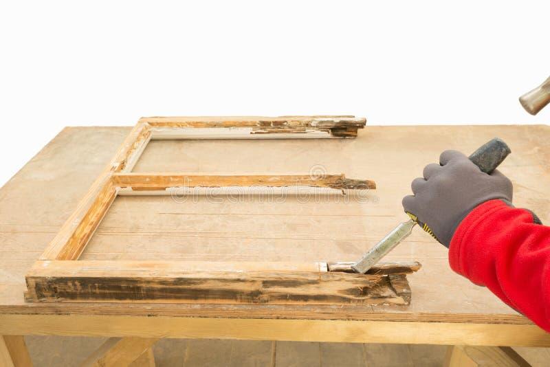 使用凿子的木匠,当修理老窗扇时 免版税库存照片