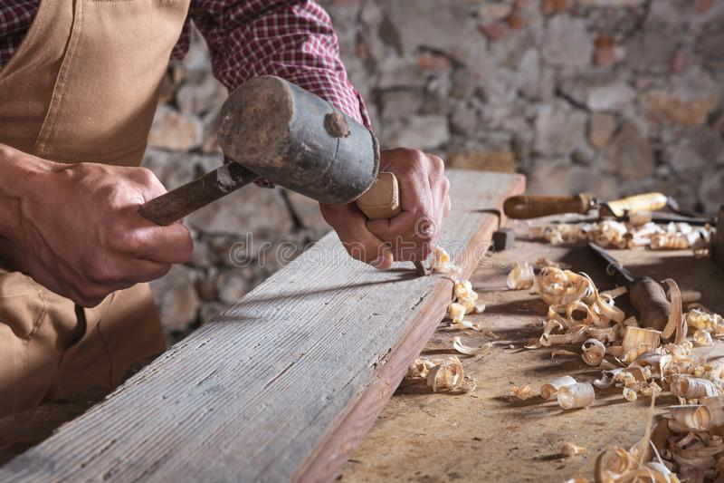 使用凿子的木工使光滑在木头下 免版税库存照片