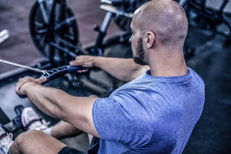 使用划船器的男性在健身房锻炼 做在健身机器的年轻人锻炼在健身房 r 穿戴在运动服 免版税库存照片