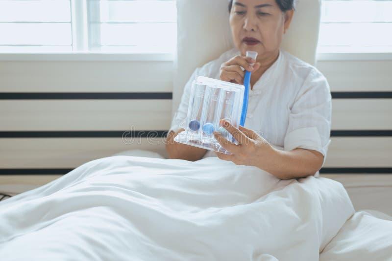 使用刺激性肺量计或三个球的耐心老年人妇女为刺激肺在卧室 免版税库存图片
