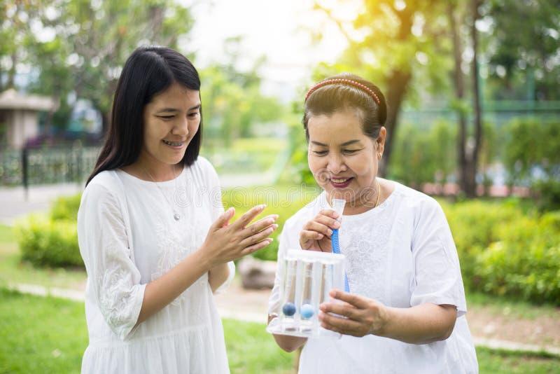 使用刺激性肺量计的年长亚裔母亲或三个球为刺激肺,鼓励女儿小心和支持 免版税库存图片