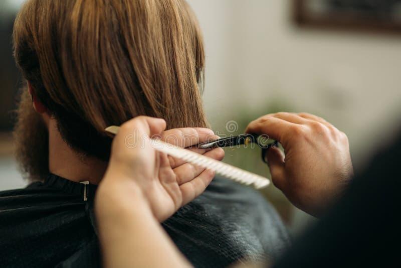 使用剪刀和梳子的理发师在理发店 图库摄影