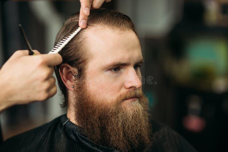 使用剪刀和梳子的理发师在理发店 库存照片
