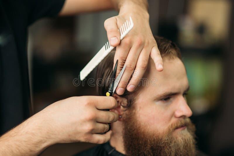 使用剪刀和梳子的理发师在理发店 库存图片