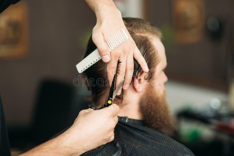 使用剪刀和梳子的理发师在理发店 免版税库存照片
