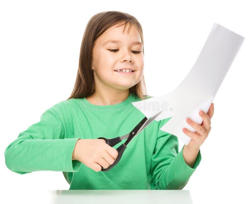使用剪刀,小女孩切开纸 免版税库存照片