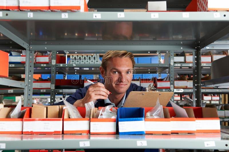 使用剪贴板的工厂劳工在储藏室 免版税图库摄影