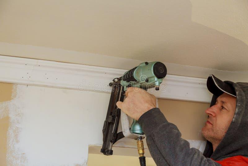 使用加冠钉子的枪的木匠曲头钉铸造的修剪,警告标记那所有电动工具 免版税库存照片