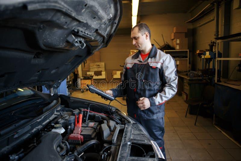 使用助推器的技工缚住对起动发动机 免版税图库摄影