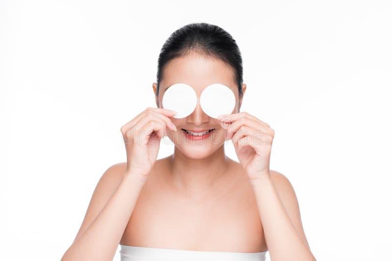 使用化装棉,年轻亚裔女孩对面孔皮肤放松关心 库存照片