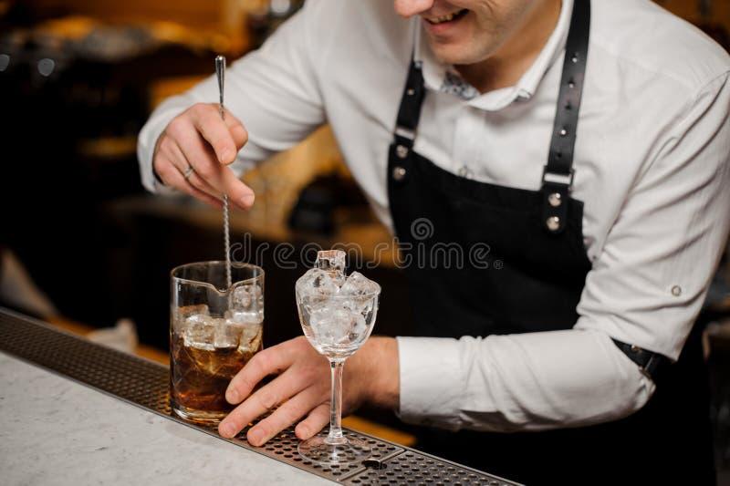 使用匙子,男服务员混合在威士忌酒的冰 免版税库存照片