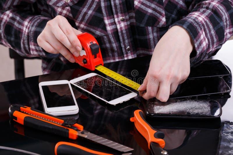 使用卷尺,测量一个残破的智能手机的长度女孩的手 特写镜头 免版税库存照片
