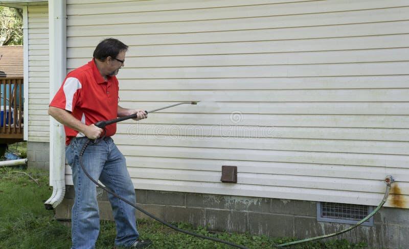 使用压力洗衣机的承包商清洗乙烯基房屋板壁 库存照片
