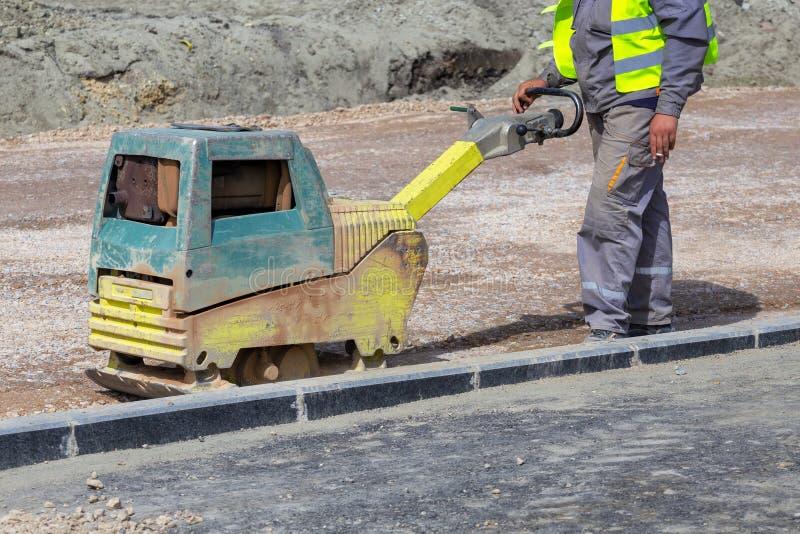 使用压紧机的工作者变紧密的土壤在城市公园2 免版税库存照片