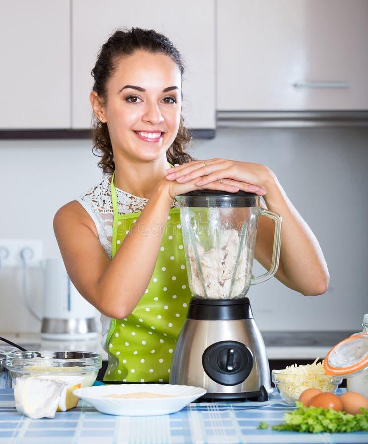 使用厨房搅拌器的微笑的女孩为烹调 库存图片