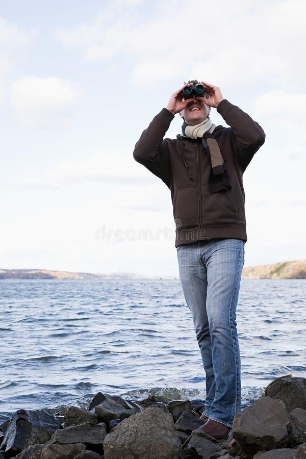 使用双筒望远镜的一个人 免版税图库摄影