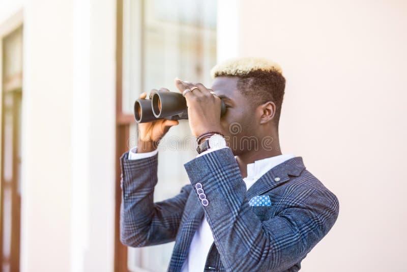 使用双筒望远镜的坚定的年轻非裔美国人的商人在办公室 库存图片