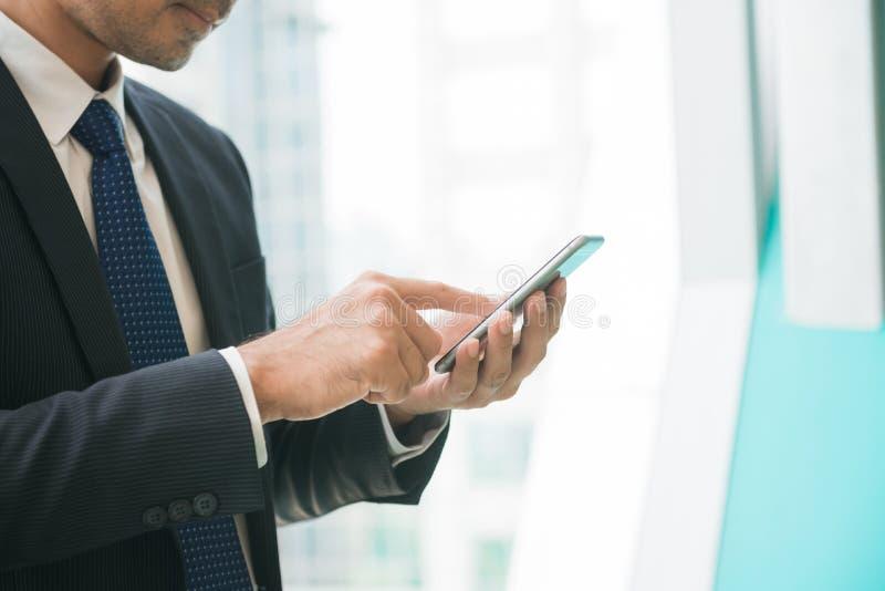 使用发短信在办公室外面的手机app的商人在有摩天大楼大厦的都市城市在背景中 免版税图库摄影