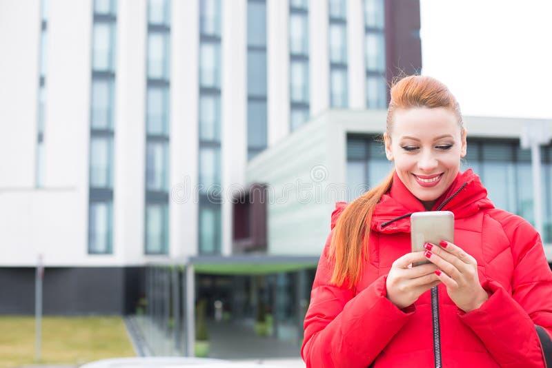 使用发短信在巧妙的电话的愉快的妇女户外在城市大厦背景 库存照片