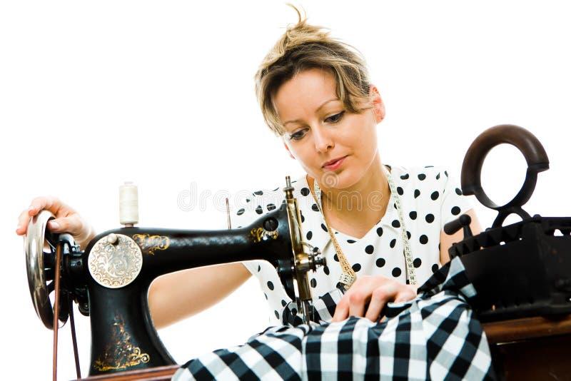使用古色古香的缝合的手工机器-葡萄酒裁缝的工具的愉快的可爱的妇女裁缝 免版税库存照片