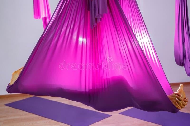 使用吊床的妇女的剪影 做瑜伽锻炼的少妇在演播室 库存图片