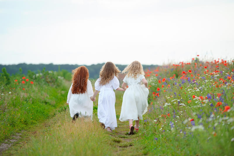 使用后面观点的孩子户外 三个女孩跑的运动的a 库存照片